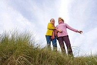 Mother and daughter on sand dune, smiling, low angle view