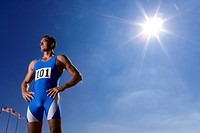 Male athlete with hands on hips, low angle view sun flare