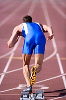 Male athlete by starting blocks, rear view (thumbnail)
