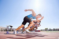 Male sprinters leaving starting blocks, low angle view sun flare (thumbnail)