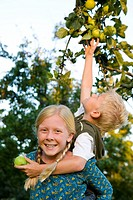 Boy 7-9 on sister's 11-13 back, reaching for apple, portrait of girl smiling