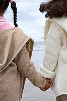 Sisters 5-9 holding hands on beach, rear view (thumbnail)