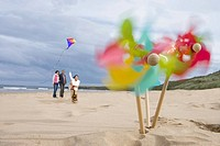 Pinwheels on beach, family with kite in background blurred motion