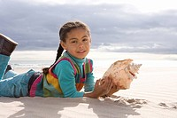 Girl 5-7 with shell on beach, portrait