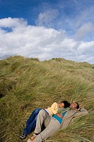 Young couple lying on sand dune, elevated view