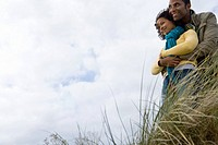 Young couple on sand dune, man embracing woman, low angle view