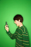 Portrait of Caucasian teen boy screaming at cell phone.