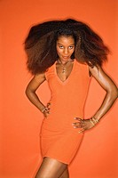 Sexy young African_American adult woman with big hair on orange background wearing dress and looking seductively at viewer.