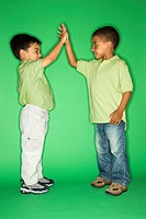 Hispanic and African American male child giving high five.
