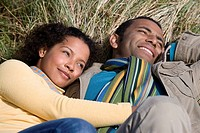 Young couple lying on sand dune