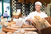 Female baker with basket of baguettes in bakery, smiling