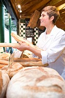 Female baker with baguettes in bakery, smiling, side view (thumbnail)