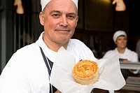 Baker with pie, smiling, portrait, close-up (thumbnail)
