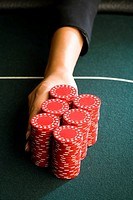 Woman pushing gambling chips onto table, close-up of hand (thumbnail)