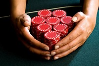 Woman with hands around piles of gambling chips on table, close-up (thumbnail)