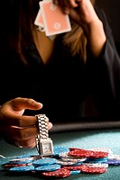 Woman placing watch on pile of gambling chips on table, mid section