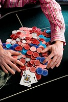 Man collecting pile of gambling chips on table, mid section, elevated view (thumbnail)