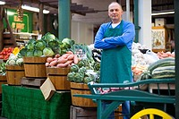 Green grocer with arms crossed by produce, portrait (thumbnail)