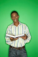 Portrait of smiling African_American teen boy holding a book standing in front of green background.