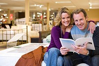 Young couple in furniture shop, woman embracing man with brochure, smiling, portrait