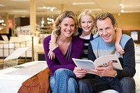 Young couple in furniture shop, daughter 6-8 embracing parents with brochure, smiling, portrait