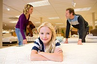 Girl 6-8 on bed in furniture shop, parents in background, smiling, portrait