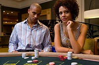 Young man and woman gambling at poker table, portrait (thumbnail)