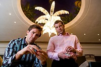 Two young men with gambling chips, portrait, low angle view