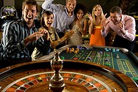 Men and women gambling at roulette table in casino, smiling, elevated view