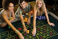 Woman and friends placing gambling chips on roulette table, portrait, elevated view (thumbnail)