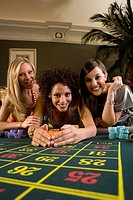 Young woman collecting pile of gambling chips from roulette table, flanked by friends, smiling, portrait