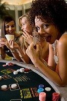 Young woman gambling at poker table in casino, showing cards, smiling, portrait