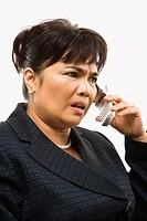 Filipino middle_aged businesswoman talking on cell phone against white background.