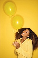 Portrait of smiling young African_American adult woman on yellow background holding balloons.