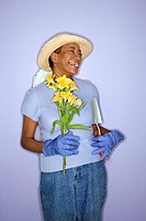 African American mature adult female with hand shovel and flowers.