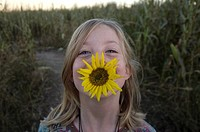 A young girl plays with a sunflower at a pumpkin patch near Roca, NE.