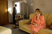 A man comes home to his wife talking on the phone.