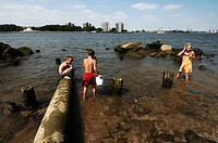 Port of Rotterdam, Heyplaat, summertime, children swimming close to a waste pipe in the new meuse