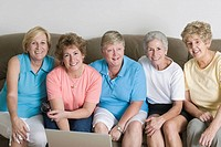 Portrait of a group of middle_aged women sitting together on a couch and smiling