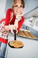 Portrait of a woman holding baked cookie on food turner.