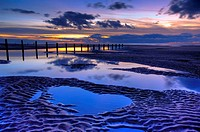 beach and wooden groyne at sunset with large pools of water and cloud reflections blackpool lancashire england uk europe