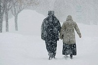 Couple walking during snowstorm
