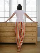 Mid adult woman wearing pyjamas looking out window, rear view