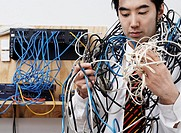 Young man wrapped with tangled computer cord