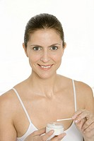 Woman holding cotton swab and jar of moisturizer, smiling at camera