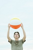Teenage boy holding up beach ball, looking at camera