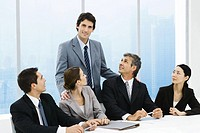 Business leader standing behind group of colleagues at meeting table, smiling at camera
