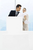 Businessman standing by lectern, female assistant holding up documents for him