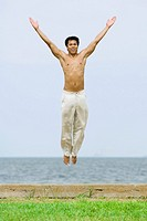 Man jumping in the air with arms raised, smiling at camera, the sea in background