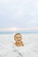 Little boy at the beach, smiling at camera, portrait